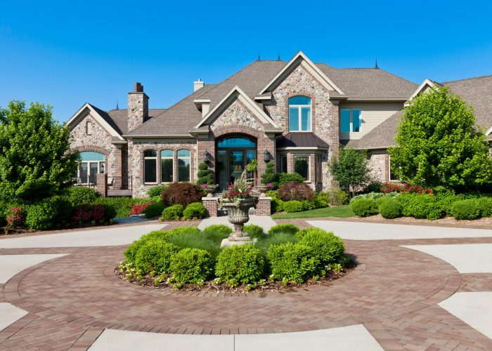 luxury residential home with large circular brick paved driveway